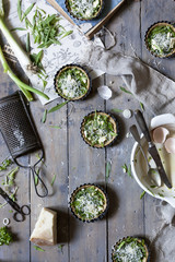 group of little quiche with green fresh herbs and Parmesan cheese on wooden table