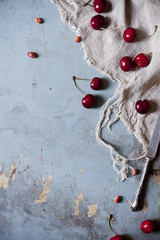 juicy whole fresh cherries from above on rustic surface with knife and cloth