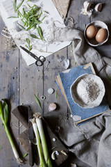 fresh spring onions on rustic kitchen table with ingredients