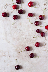 juicy whole fresh cherries from above on pink marble surface