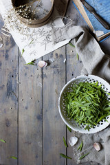 edible seasonal wild herbs on plate on a rustic kitchen table