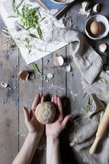 hands holding bread dough over table with rolling pin and ingredients