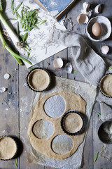 Cutting dough into circles. Preparation of little quiche on a kitchen table with ingredients