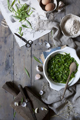 cooked seasonal wild herbs on rustic kitchen table with ingredients and tools