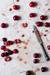 cutting juicy fresh cherries on marble surface with a knife