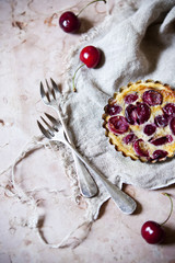 one little cherries clafoutis on table with two forks and cloth