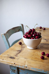 freshly picked cherries on bowl on rustic wooden table
