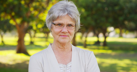 Senior woman standing in the park looking at camera