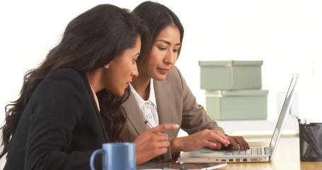 Japanese and Mexican businesswomen working on laptop