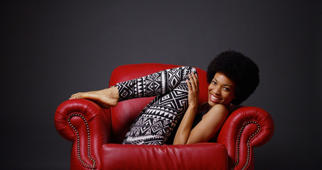 African woman in red leather arm chair kicking legs playfully