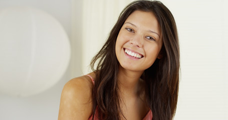 Attractive Hispanic woman playing with hair and smiling at camera