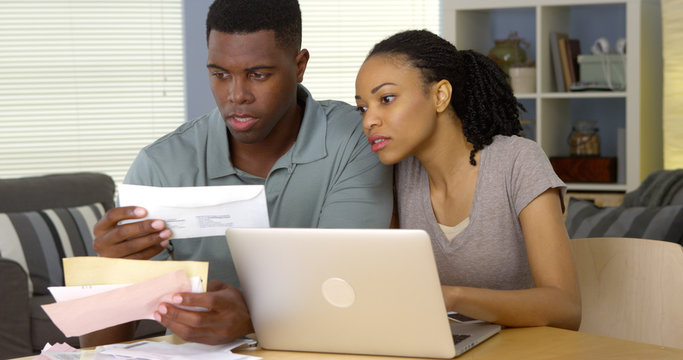 Serious young black couple paying bills online with laptop computer