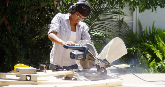 Black woman doing home improvement cutting wood with a table saw