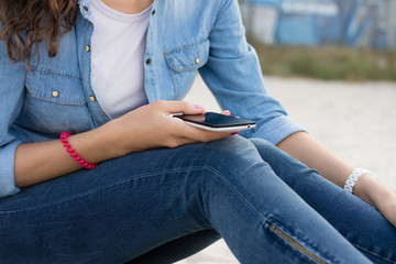 Young woman in a denim dress resting on the beach with a phone i