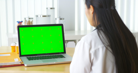 Chinese doctor talking to laptop with green screen