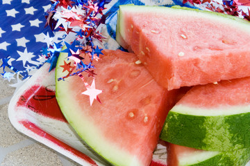Holiday Watermelon – Slices of fresh watermelon, surrounded by patriotic red, white, and blue decorations.