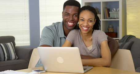 Happy young black couple with laptop and bills