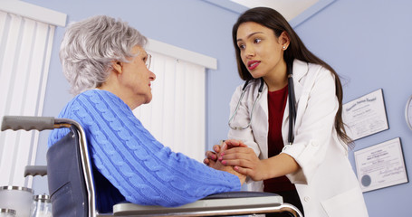 Hispanic woman doctor comforting disabled elderly patient