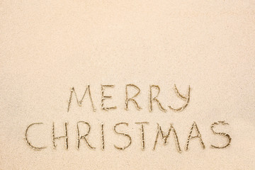 Merry Christmas inscription on wet yellow beach sand