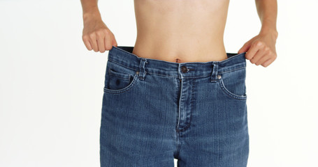 Skinny woman holding up  big jeans