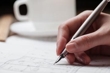 woman holding a pen over a house blueprint