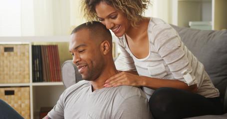Black girlfriend giving boyfriend neck massage