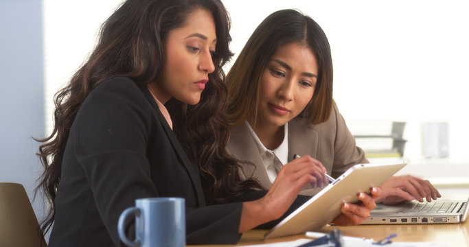 Mexican businesswoman sharing findings on tablet with Japanese colleague