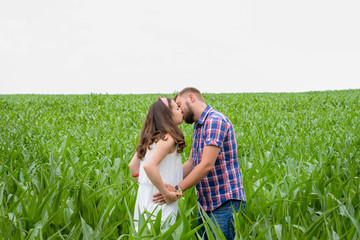 Happy young adult couple in love spending time on the field on sunny day outdoors. Handsome man and beautiful woman standing and kissing. Romance and love concept
