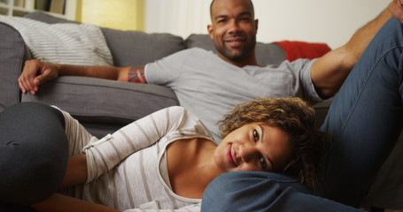 Cute African American couple sitting on floor looking at camera