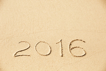 2016 inscription written in the wet yellow beach sand
