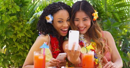 Two fun girls taking selfie on tropical vacation
