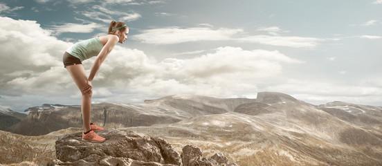 Female runner resting on mountain peak