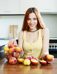 beautiful woman with peaches at table