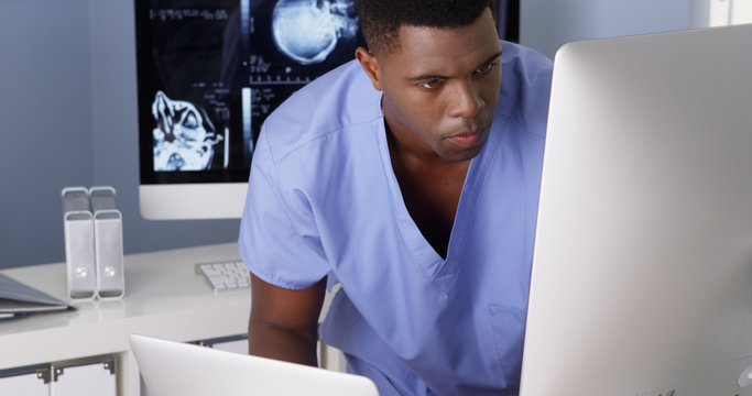 Young Black doctor working on multiple computers