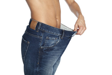 Mid section of slim woman wearing too big jeans on white background