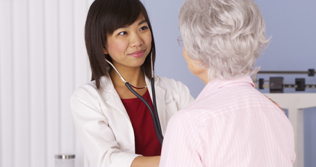 Chinese doctor listening to senior patient's heart