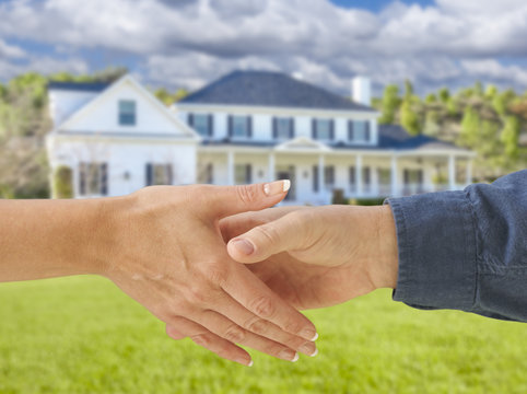 Man and Woman Shaking Hands in Front of New House