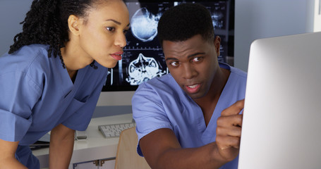 Two African American Medical specialists using computers