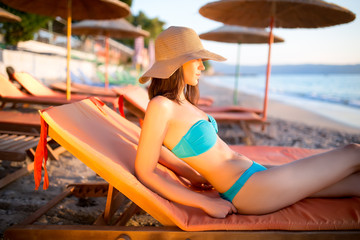 Beautiful woman sunbathing in a bikini on a beach at tropical travel resort,enjoying summer holidays.Young woman lying on sun lounger near the sea.Beach sunset and golden light.Woman in hat and bikini