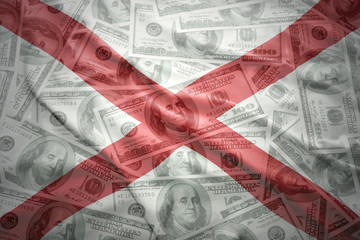 colorful waving alabama state flag on a american dollar money background
