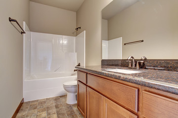Simplistic bathroom with marble counters, and tile floor.