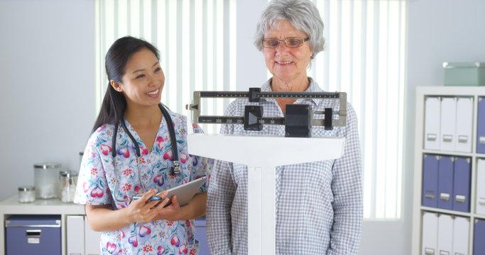 Chinese nurse weighing elderly patient