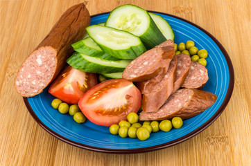Sausage, tomatoes, cucumbers, green peas in blue plate on table