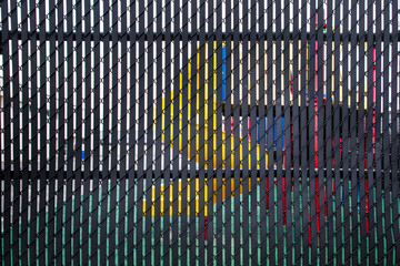 Childrens playground barely visible behind metal privacy fence