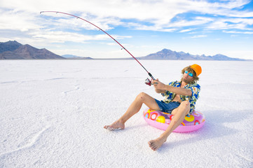 Redneck American fisherman wearing Hawaiian shirt goes on cheap ice fishing vacation holiday with inflatable pink ring in white desert