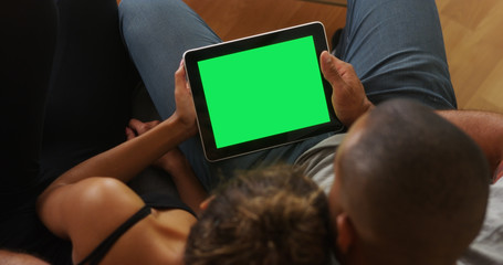 African couple holding tablet with greenscreen