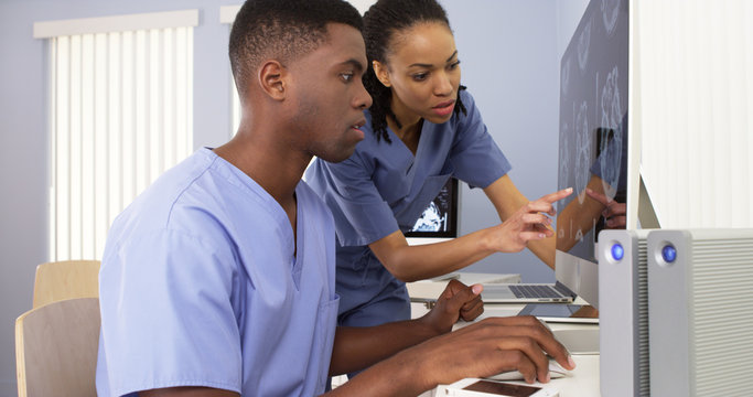 Two African American medical specialists working together on computer