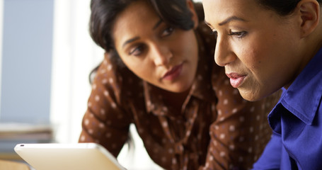 African American and Hispanic business women using tablet computer