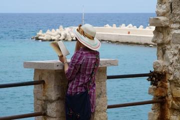 Rilassarsi leggendo un libro in riva al mare