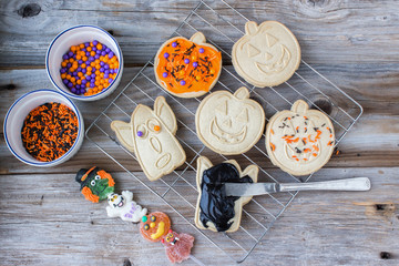 horizontal image of freshly baked halloween cookies on a baking rack with icing and decorative candy sprinkles sitting in a dish ready to be spread on cookies on old wood background